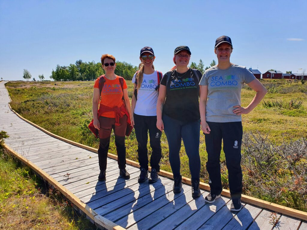 Four smiling women standing in Sandskär with SeaCOMBO t-shirts on.