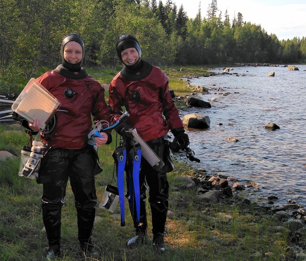 Two persons in drysuits standing on the shoreline
