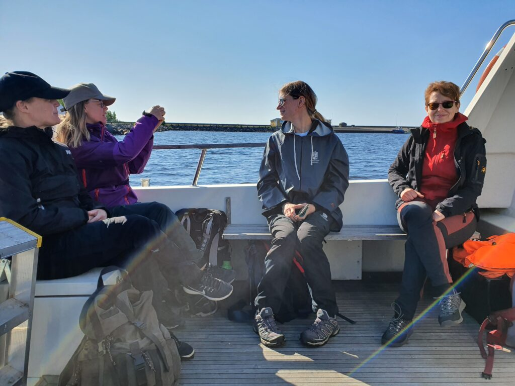 Four happy persons sitting at the back of an boat out in the sea.